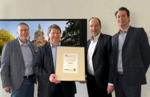 Bereichsleiter SAM, Oliver Schäpe (ganz rechts), überreicht das U-S-C SAM Zertifikat an die Verantwortlichen der Landeshauptstadt Hannover (von links nach rechts: Herr Kropp, Herr Rackow und Bereichsleiter Herr Vogel) als Compliance Nachweis für Microsoft und Wirtschaftsprüfer